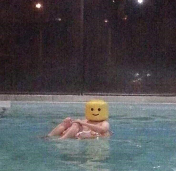 cursed images - man in pool wearing a lego head