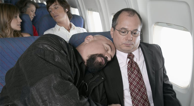 Awkward picture of a guy sleeping on another guy's shoulder on a plane
