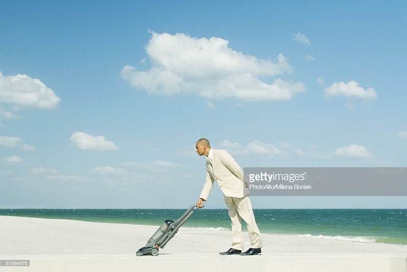 Man in a suit vacuuming a beach