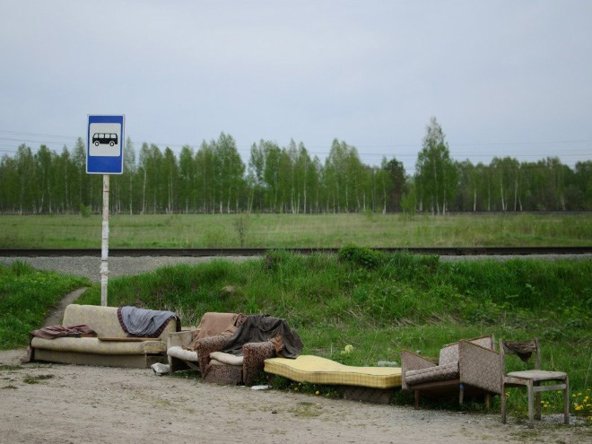 A bus stop with some couches and chairs around it