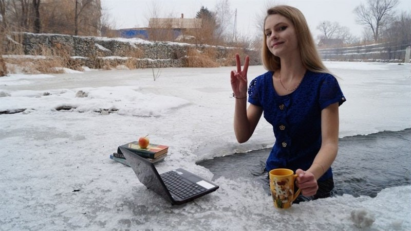 girl sitting in snow with laptop and coffee