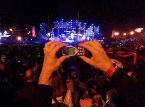 memes - Crowd concert person taking a pic with an old phone