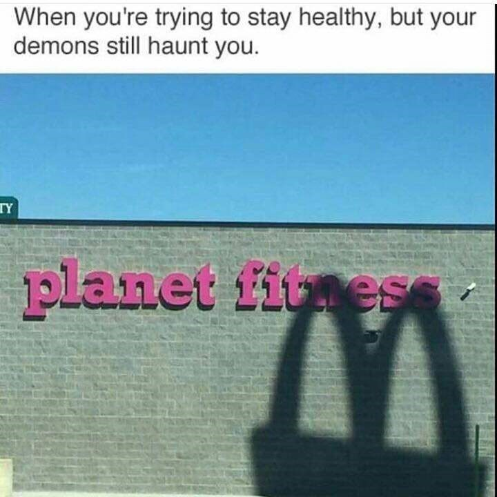 Photo of a McDonald's sign shadow over a Planet Fitness