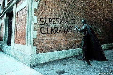 "Batman writing on a brick wall, ""Superman is Clark Kent"""