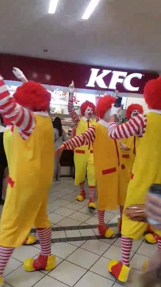 picture of several people dressed as Ronald McDonald in front of a KFC store