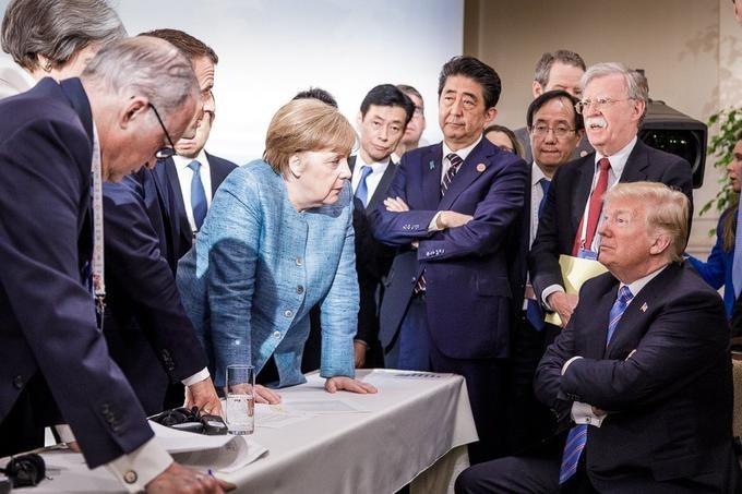 Original photo of Angela Merkel leaning over a table talking to Trump who looks unamused