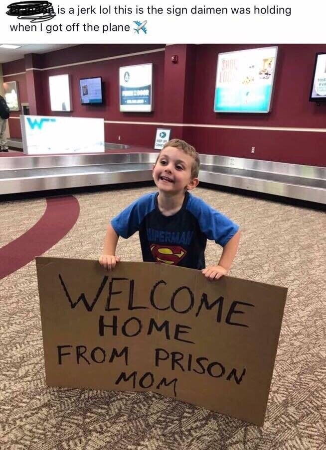 pic of child at the airport holding a sign welcoming mom from prison