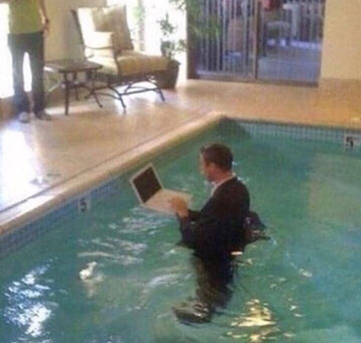 cursed_image - Swimming pool man using a laptop