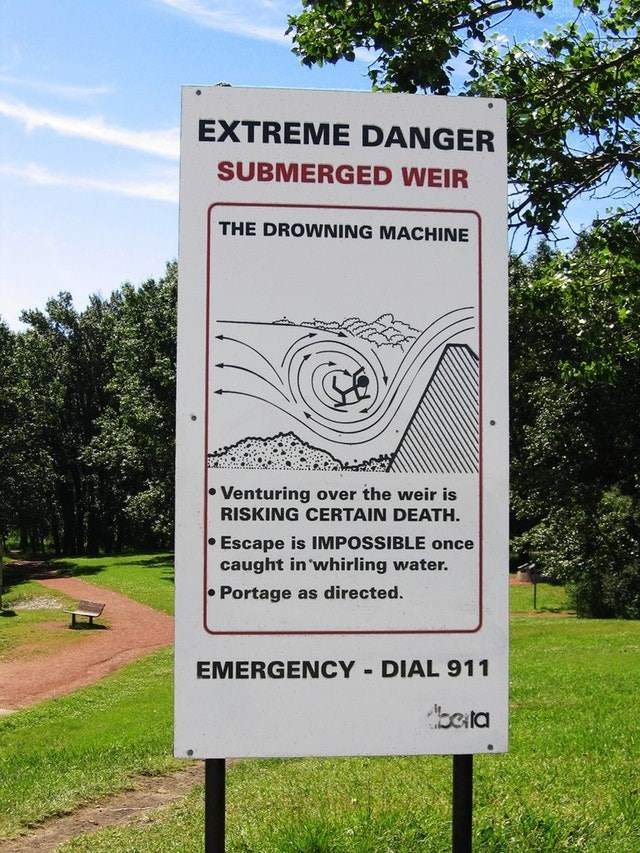 Nature reserve - EXTREME DANGER SUBMERGED WEIR THE DROWNING MACHINE Venturing over the weir is RISKING CERTAIN DEATH Escape is IMPOSSIBLE once caught in whirling water. Portage as directed. DIAL 911 EMERGENCY bela