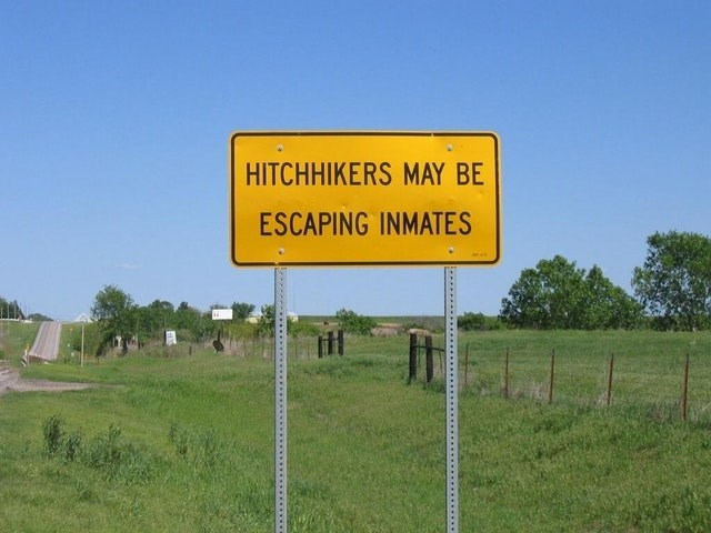 Sign - HITCHHIKERS MAY BE ESCAPING INMATES