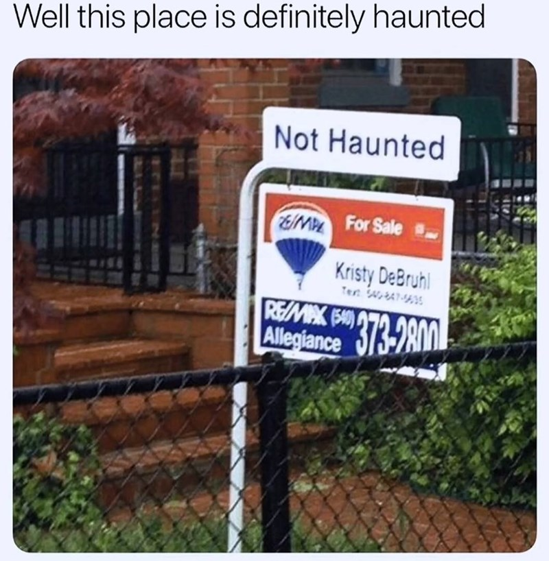 "For sale sign on a house that says, ""Not haunted"""