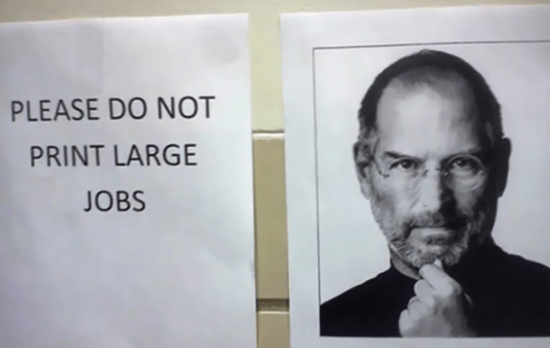 """Sign that says """"Please do not print large job"""" next to a large print photo of Steve Jobs"""