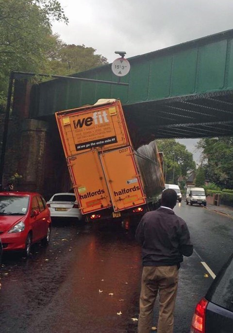 """Large truck that says """"We fit"""" that doesn't fit under a bridge"""