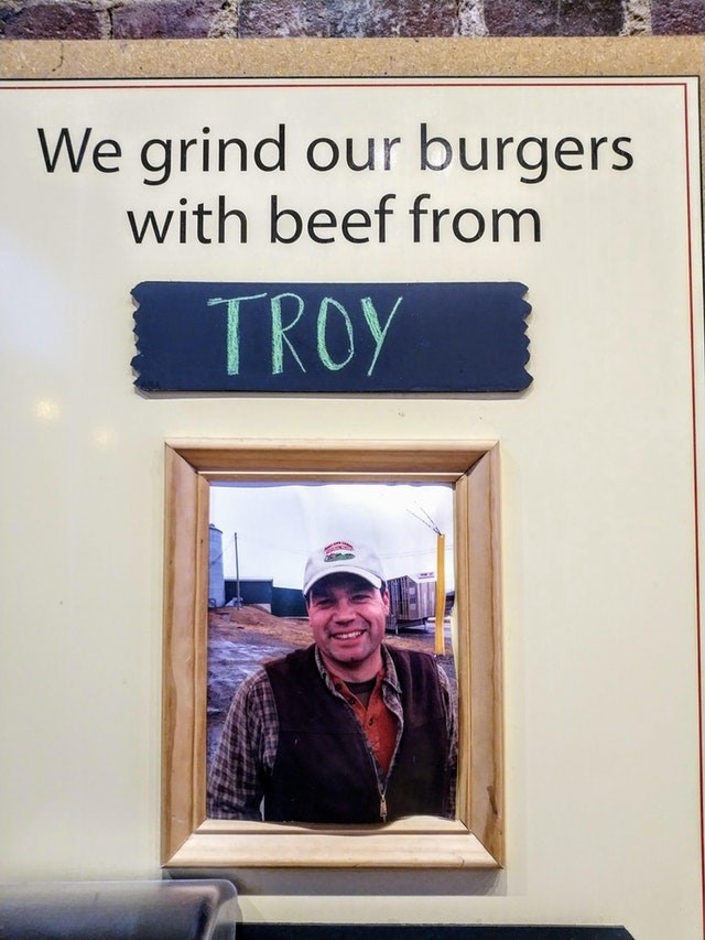 Text - We grind our burgers with beef from TROY