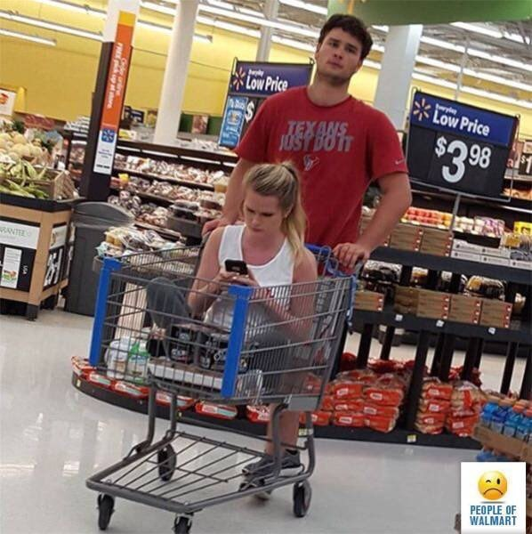 Pic of a guy pushing his girlfriend around in a shopping cart at Walmart