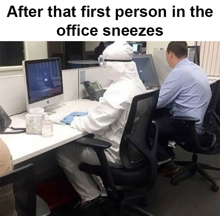 "Picture of a person sitting at a desk wearing a hazmat suit under the caption, ""After that first person in the office sneezes"""