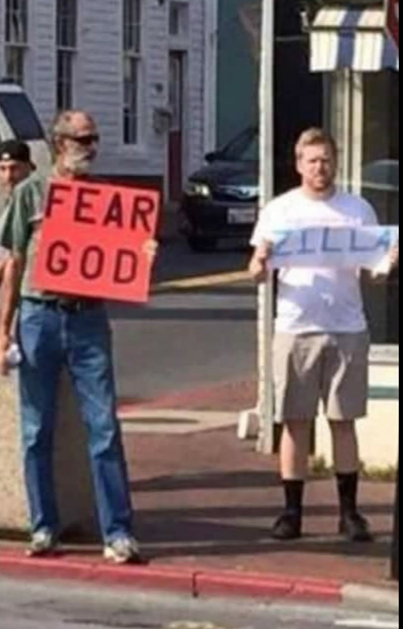 Picture of someone holding a 'Fear God' sign next to someone else holding a sign that says, 'Zilla'