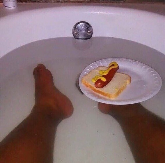 Pic of someone's legs in a bathtub with a hotdog on a piece of bread floating on a plate