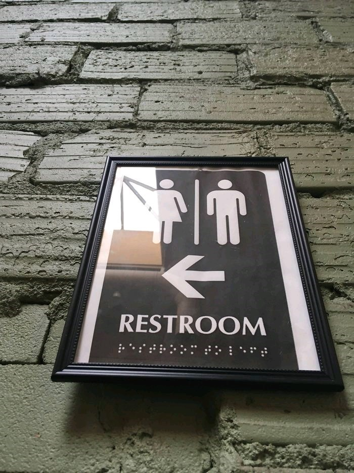 picture of framed bathroom sign with Braille under the glass
