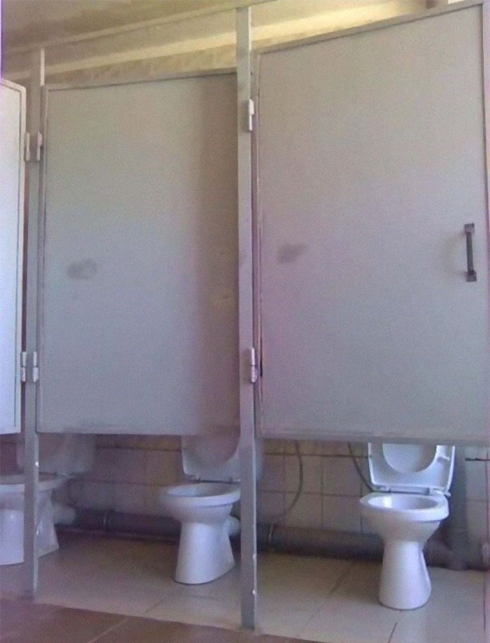 picture of bathroom stalls doors with gaps tall enough to reveal the toilets
