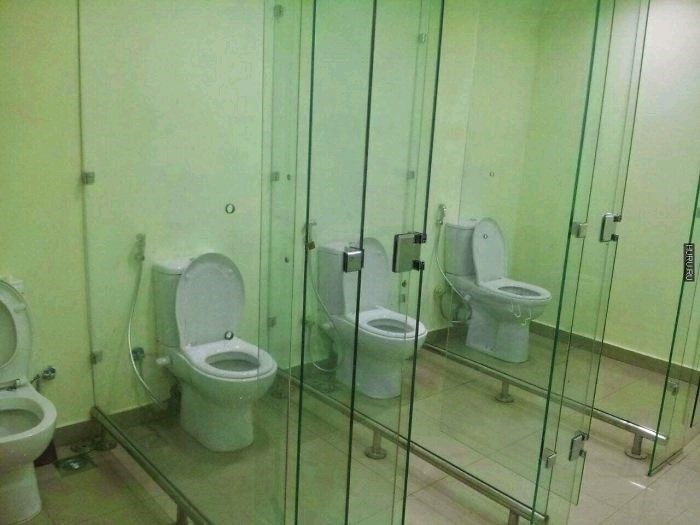 picture of bathroom stalls with clear walls between them