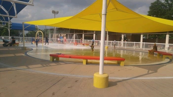 picture of yellow awning over pool reflecting in the water and giving it a yellow hue