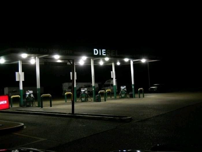 """gas station at night with broken neon sign spelling """"die"""" instead of """"diesel"""""""