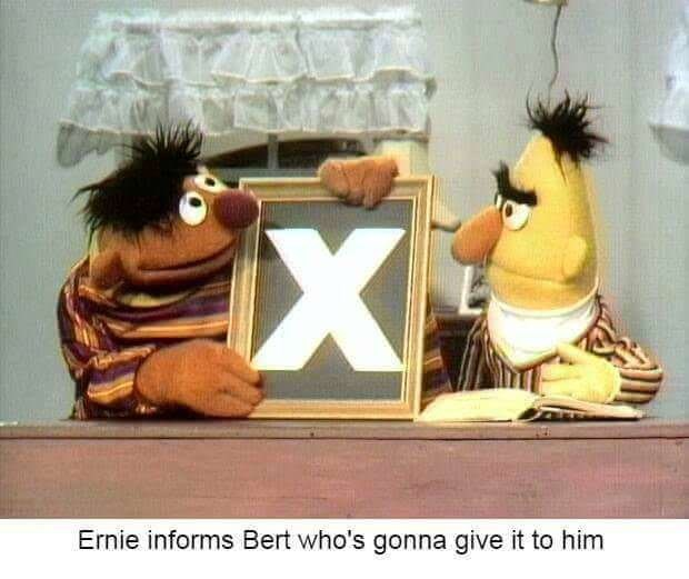 "Ernie showing Bert a framed picture of the letter X under the caption, ""Ernie informs Bert who's gonna give it to him"""