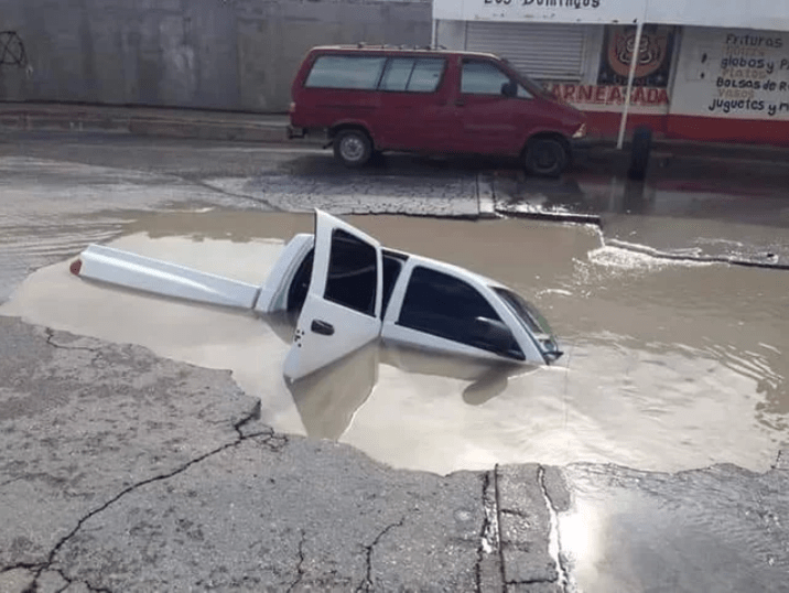 picture of car almost entirely drowned in sink hole