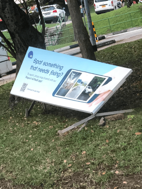 picture of broken down sign advertising a fault report app