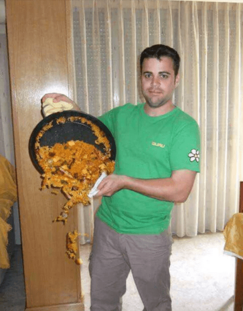 picture of man proudly holding up pan with the food in it falling out as the picture is being taken