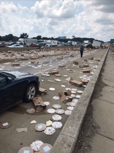 picture of street littered with frozen pizzas and cardboard boxes
