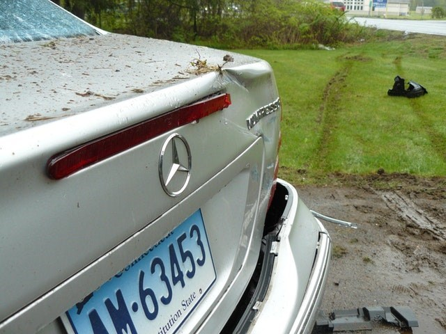 picture of dented rear of car next to wheel tracks in grass from the car that had hit it