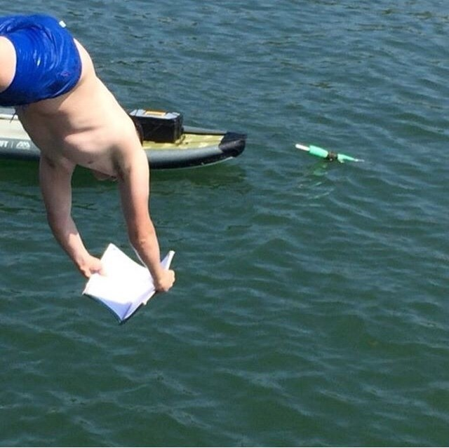 cursed image of person diving into water while holding book