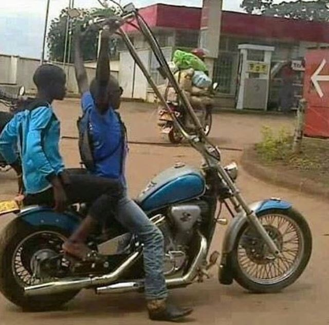 cursed image of person driving motorcycle and straining to hold onto too tall handlebars