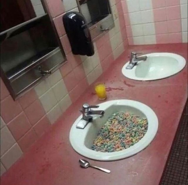 cursed image of public bathroom sink filled with cereal with spoon next to it