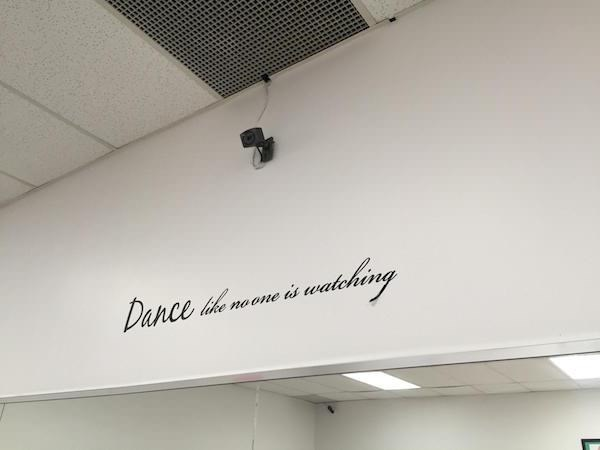 "Sign on the wall that says, ""Dance like no one is watching"" right below a very obvious camera"