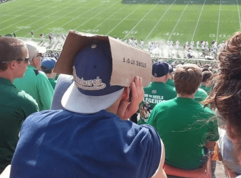 man using a carton to block the sun from his eyes while wearing a backwards baseball cap
