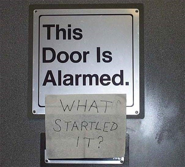pic of a door sign that says there is an alarm and someone wrote what started it