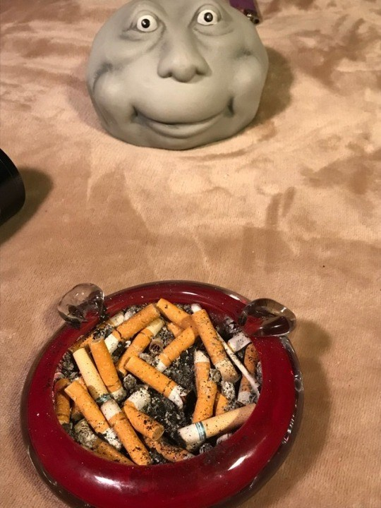 cursed_image - Dish filled with cigarettes and creepy face