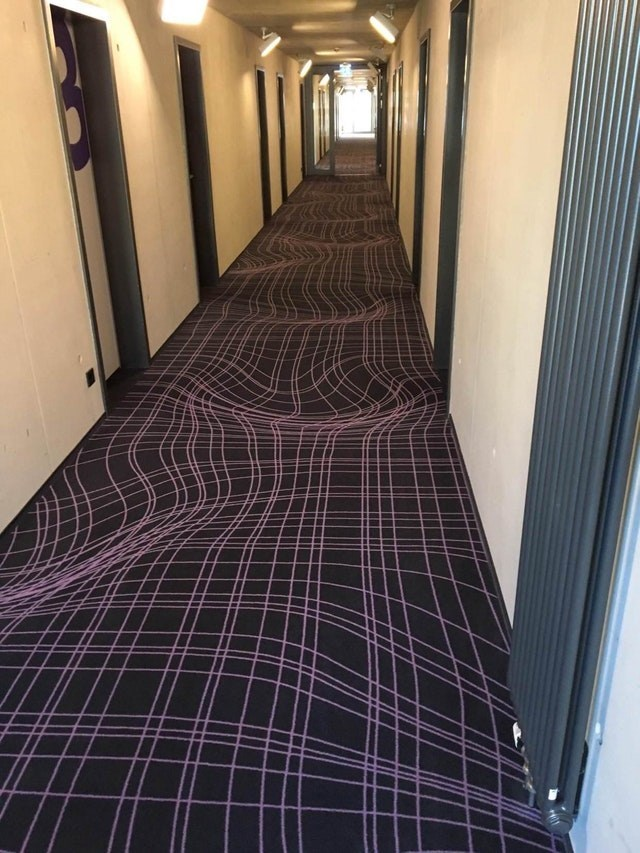 picture of squiggly patterned carpet that makes corridor floor appear to have dents in it