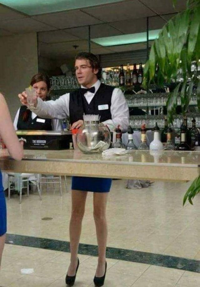 picture of bartender standing behind reflective bar and appearing to have feminine legs