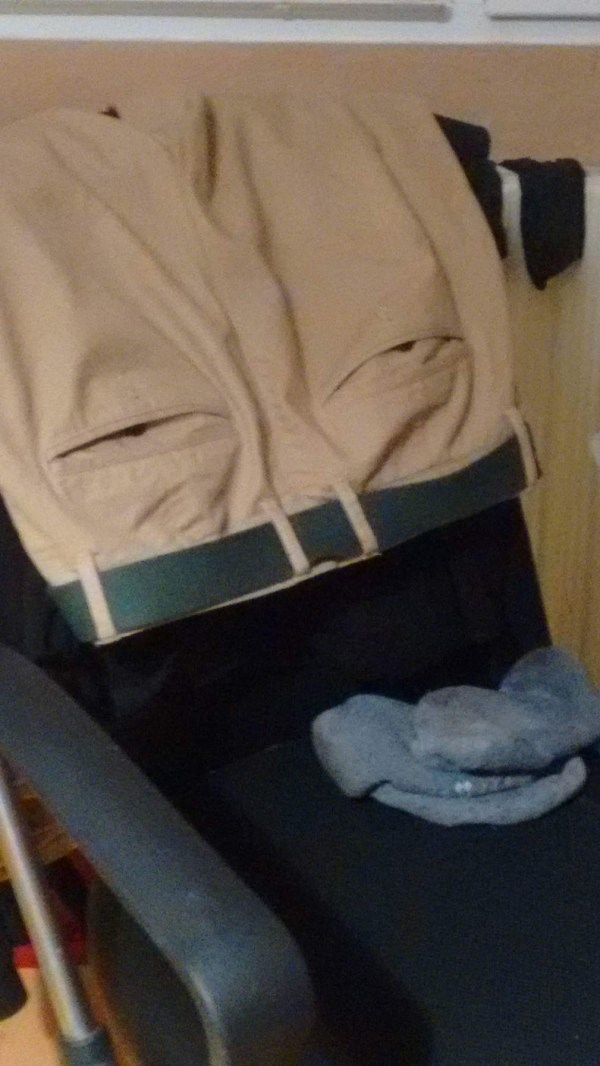 picture of pants and socks thrown over chair creating a weary looking face
