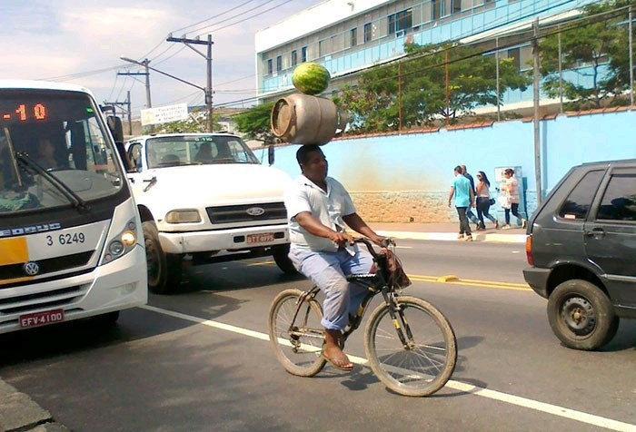 pic of a person riding a bike and balancing a watermelon and a barrel on his head and defying gravity