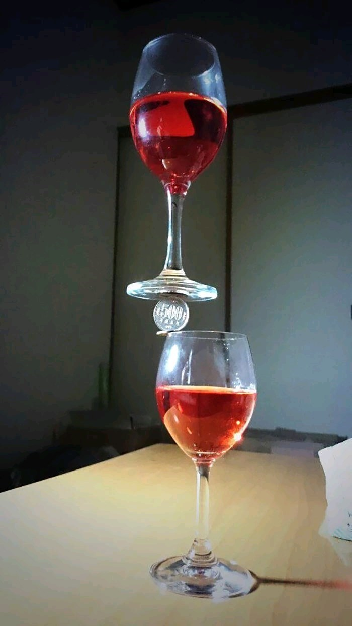 pic of a wine glass balancing on a coin that is between a second wine glass and defying gravity