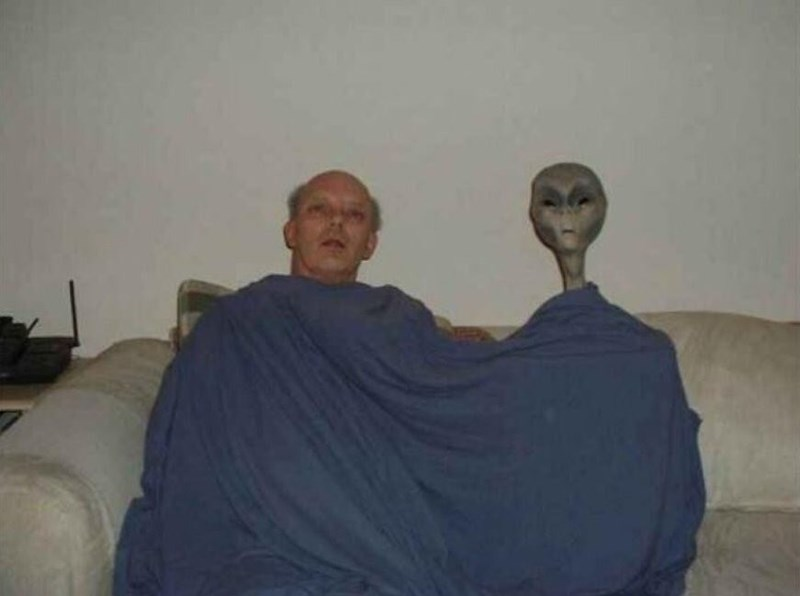 Cursed Image of a man and alien sitting together under a blanket while staring ahead