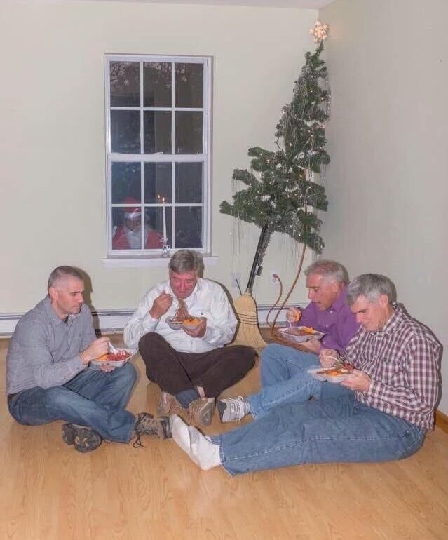 Cursed Image of four older men sitting on the floor of a living room while eating in front of a Christmas tree