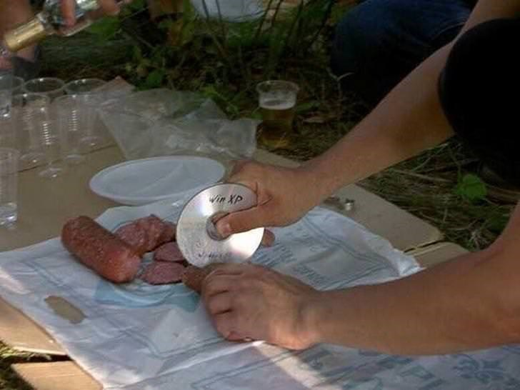 Cursed Image of a person cutting sausages with a CD