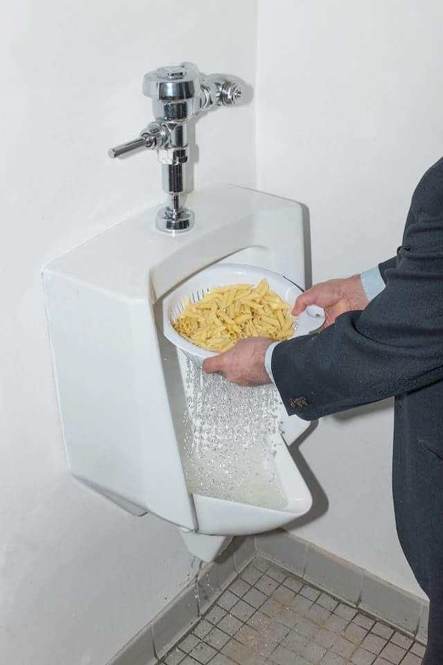 Cursed Image of someone draining water after boiling pasta into a men's urinal
