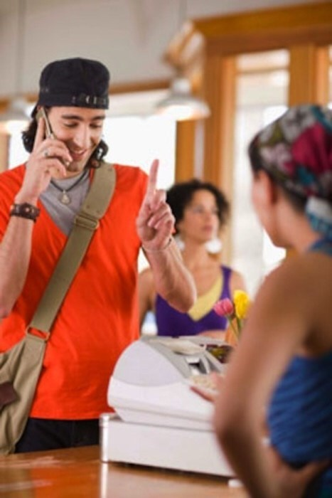 Stock photo of a guy talking on his cell phone when a cashier is waiting for him to make his order
